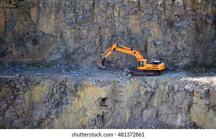 Orange excavator, digger in a granite quarry