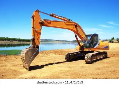 orange excavator digging earth on nature field