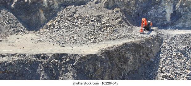 Orange excavator on a working platform. Panorama landscape