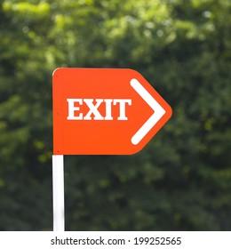 Orange Exit sign on a white post