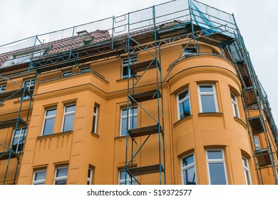 orange facaded building with construction on the roof without logos
