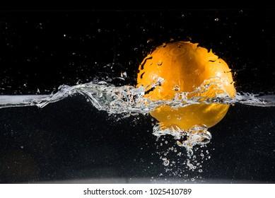 Orange falling on water