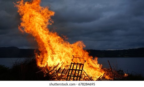 Orange fire flames. Big fire outside city at sant hans day in Drammen, Norway