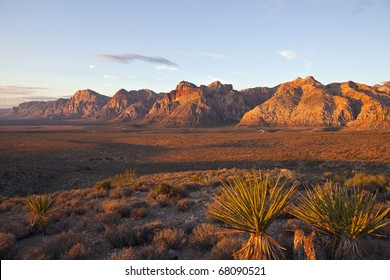 Orange first rays of dawn light on the cliffs of Nevada's Red Rock National Conservation Area.