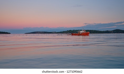 Orange fishing boat coming back to harbor in early morning being follow by a flock of seagulls.  Sky has nice hues of orangy pink