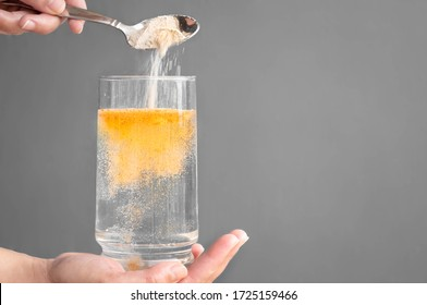 Orange fizzy powder and water glass with copy space. Healthy supplement.