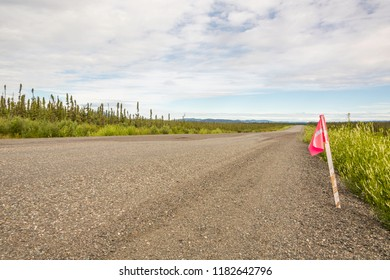 An orange flag marks permafrost damage and encourages motorists to slow down on the Alaska highway. Yukon Territory, Canada.
