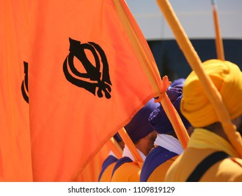 orange flag with symbol of the Sikh religion called KHANDA formed by two scimitars and men with turbans