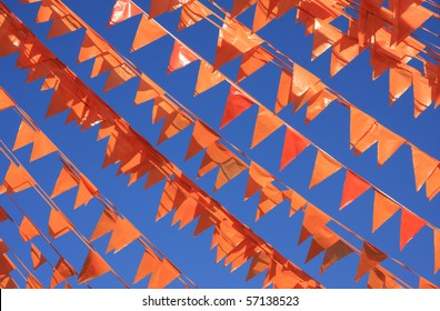 Orange flags, (also used on King's day in Holland) against a blue sky during the soccer world cup.