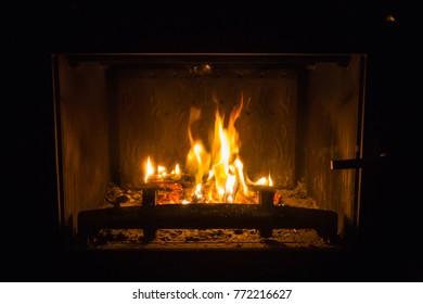Orange flames of fire in fireplace, background, orange