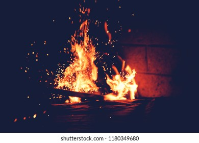 Orange flames and sparks in the fire, abstract background, warmth and comfort of home