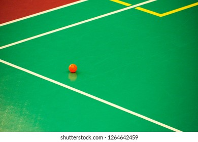 Orange floorball ball on surface