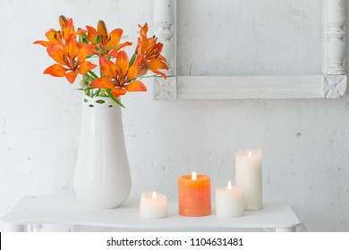 orange flowers and candles on white background