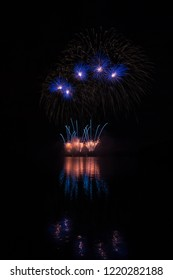 Orange fountain and blue stars fireworks over Brno's Dam with lake reflection