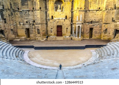 Orange, France - Dec 10th 2017 - Lonely young tourist inside the Orange's Roman Theatre, one of the greatest ancient sites in Europe
