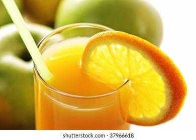 Orange fresh juice and apples closeup photo over white