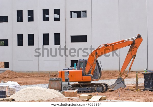 An orange front end loader at construction site with sand pile