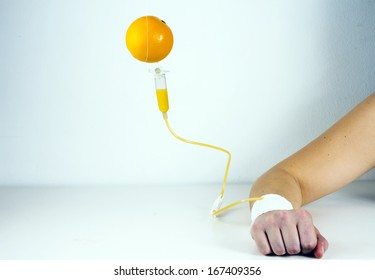 Orange fruit connected to IV drip into arm/Vitamin injection/Studio shot