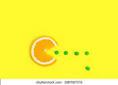 Orange fruit eating green peas on creative color paper. Trendy minimal pop art style. Food concept background