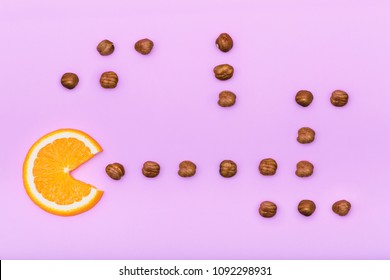 Orange fruit  eating nuts on creative color pink paper background. Trendy minimal pop art style. Concept fun with colorful food.