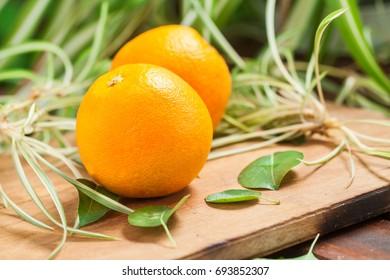 Orange fruit with green leaf on wooden cutting board