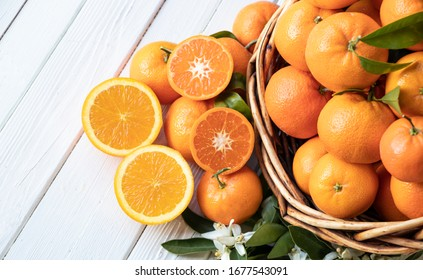 Orange fruit with green leaves on the white wood.  Home gardening. Mandarine oranges. Tangerine  oranges. Orange color. Fresh orange juice.