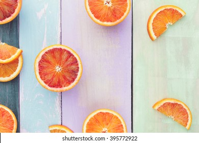 Orange fruit. Halved and wedge oranges and blood oranges on rustic board. Top view, vintage toned image, blank space