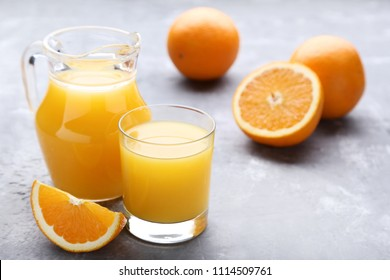 Orange fruit with jug and glass of juice on grey wooden table