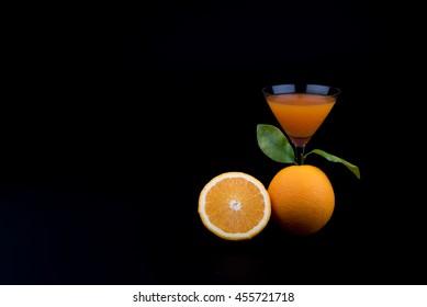 orange fruit and orange juice on black