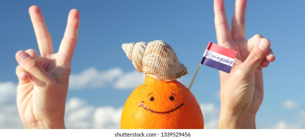 Orange fruit and Netherlands mini flag with text: KONINGSDAG - Kings day.