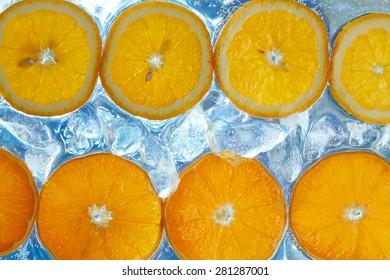 Orange fruit slices on ice cubes background