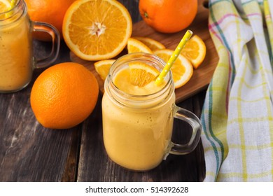 Orange fruit smoothie in the glass jar with fresh orange slices on rustic wooden background
