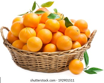 Orange fruits with green leaves in basket with one on the surface in the foreground, isolated on a white background