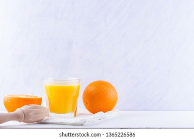 Orange fruits with juice, concept. Orange juice and halves of oranges on white background. Citrus for making juice and manual juicer. Whole and squeezed oranges and glass of juice