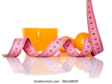 orange fruits and measuring tape on a white background to symbolize a healthy diet
