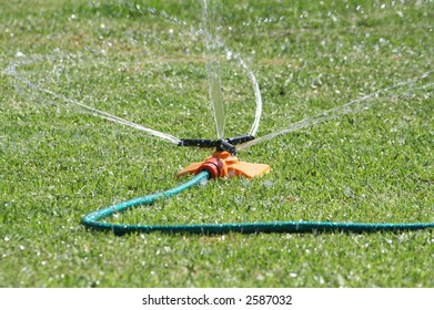 Orange garden sprinkler swirling water over green grass