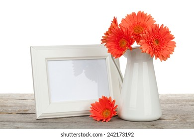 Orange gerbera flowers and photo frame on wooden table on white background