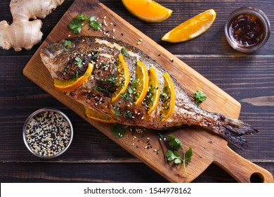 Orange ginger sea bream fish, sprinkled with sesame seeds and cilantro on serving board. Soy orange sauce. Overhead horizontal image