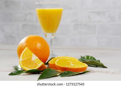 orange and glass of orange juice on a white wooden table