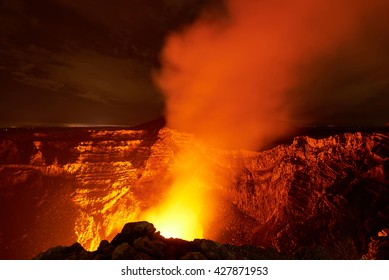orange glow coming from volcano crater  at night