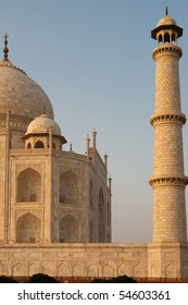 Orange glow on the fine marble details of the front corner half of the Taj Mahal and minaret are visible at evening sunset in Agra, India. Vertical