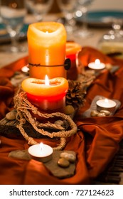 Orange glowing candles set as a holiday centerpiece