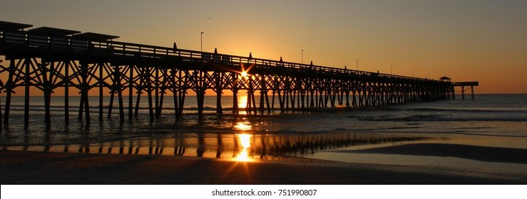 Orange glowing sunrise over the second avenue pier in Myrtle Beach, South Carolina