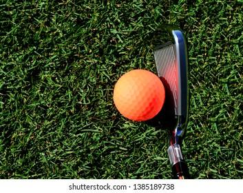 Orange golf ball ready to be hit by a golf club on a fairway