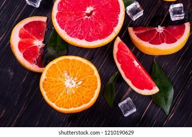 orange and grapefruit juice On a wooden black background