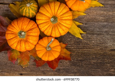 orange and green pumpkins harvest with fall leaves on wooden textured table