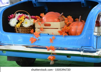 Orange and green pumpkins picking on hay haystack in country countryside store in autumn, fall for thanksgiving, halloween holidays. rustic autumn scenery, haystack, pumpkins, vintage car