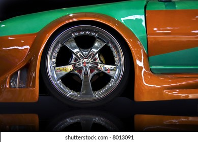 orange and green tuning car, isolated over black mirror