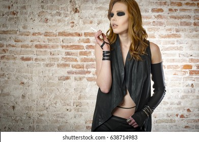 Orange hairs woman smoking in dirty place. Lady in leather jacket and pant with beauty makeup.
