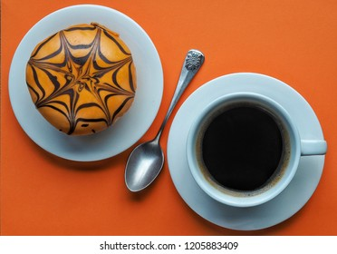 Orange halloween donut decorated with chocolate spider web and white cup of coffee on orange background.